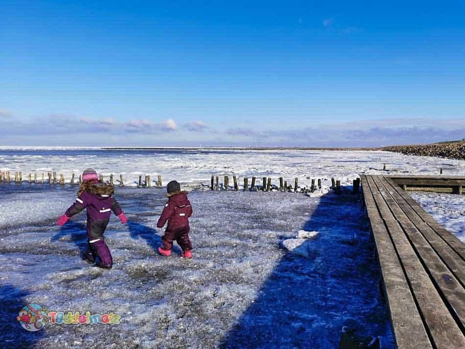 Kinder im Schneeanzug auf dem Watt